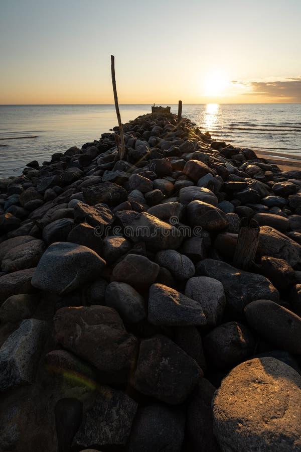 De pijlerzonsondergang van het keistrand met levendige rode en oranje kleuren op de Oostzee - Tuja, Letland - April 13, 2019 royalty-vrije stock fotografie