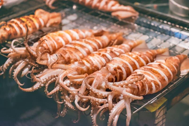 De pijlinktvis op vleespennen wordt geroosterd door een straatventer stock afbeeldingen
