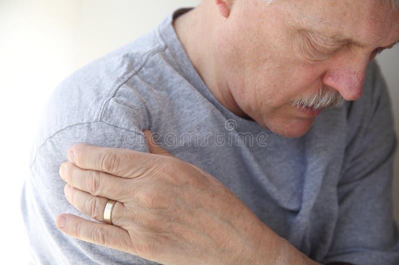 De pijn van de schouder bij een hogere mens stock foto's