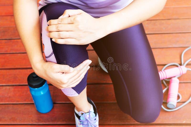 De Pijn van de knie Jonge vrouw die knie aan verwonding lijden terwijl het uitoefenen en het lopen Gezondheidszorg en sportconcep royalty-vrije stock fotografie