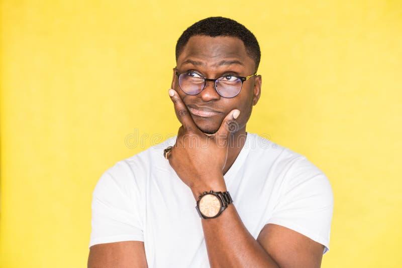De pijnlijke onzekere Afrikaanse Amerikaanse mens met glazen houdt zijn kin en de beurzen zijn lippen, ziet incredulously eruit,  royalty-vrije stock afbeeldingen