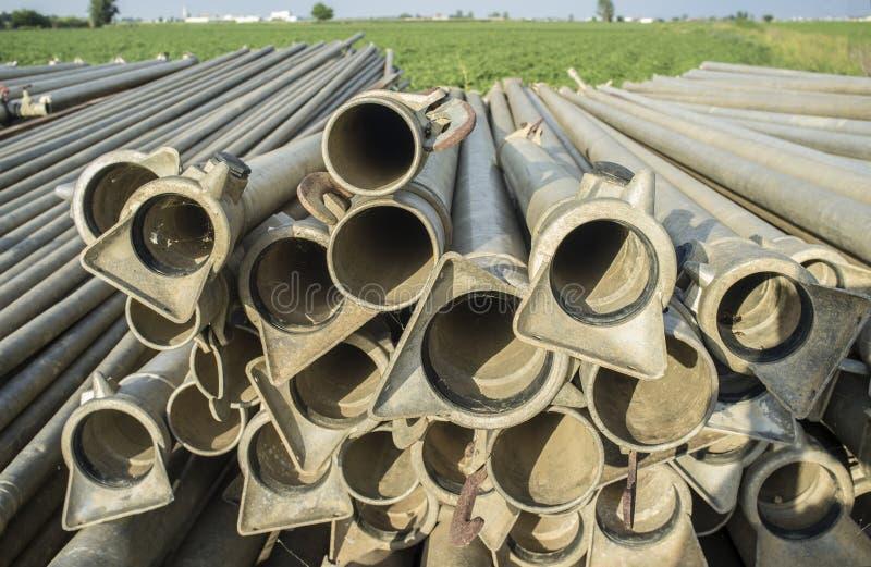 De pijpen van het irrigatiemetaal uit het water geven seizoen in openlucht worden gestapeld dat royalty-vrije stock afbeeldingen