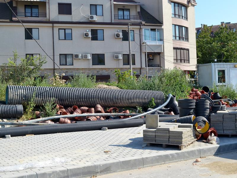 De pijpen van verschillende grootte en pallets met het bedekken plakken bij de plaats van wegenbouw werken stock afbeelding