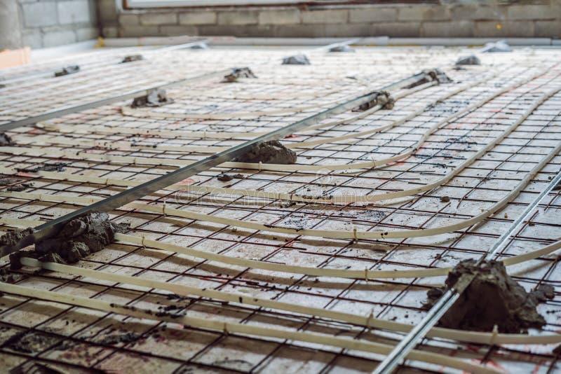 De pijpmonteur zette vloerverwarming op Verwarmingssysteem en vloerverwarming stock afbeelding