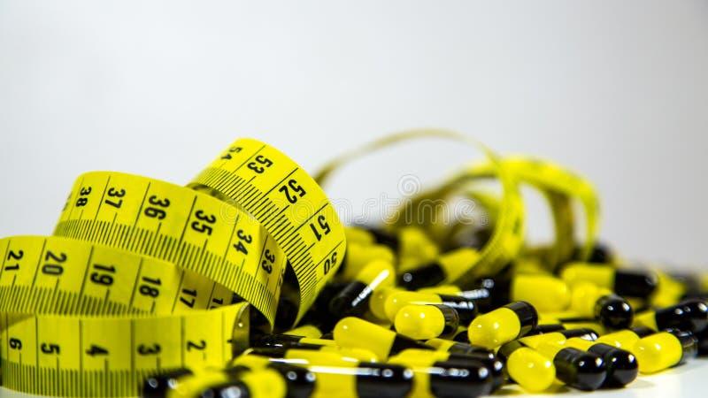 De pillen met het meten van band op witte achtergrond, vertegenwoordigen de industrie van de dieetpil royalty-vrije stock afbeeldingen