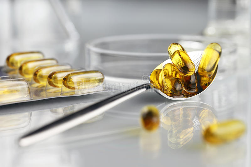 De pillen omega 3 supplementen van lepelvitaminen met blaar en petrischaal stock foto