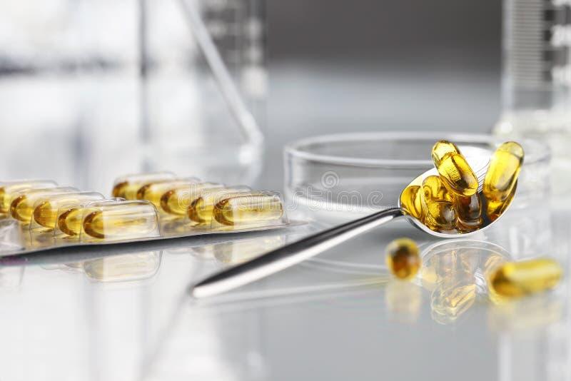De pillen omega 3 supplementen van lepelvitaminen met blaar en petrischaal royalty-vrije stock afbeeldingen