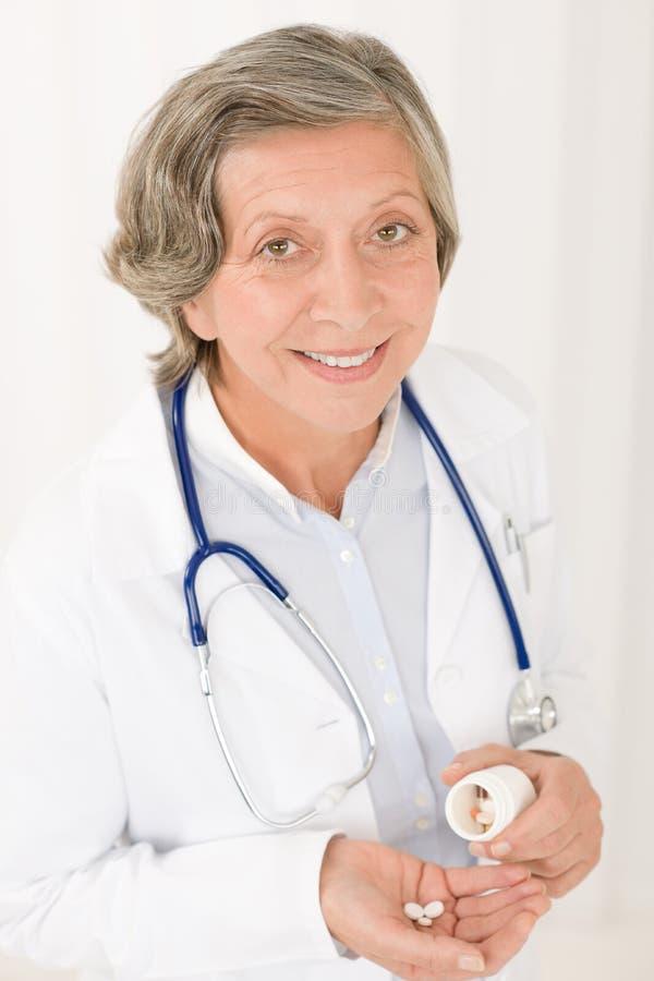 De pillen van de medische artsen het hogere vrouwelijke greep glimlachen stock foto's