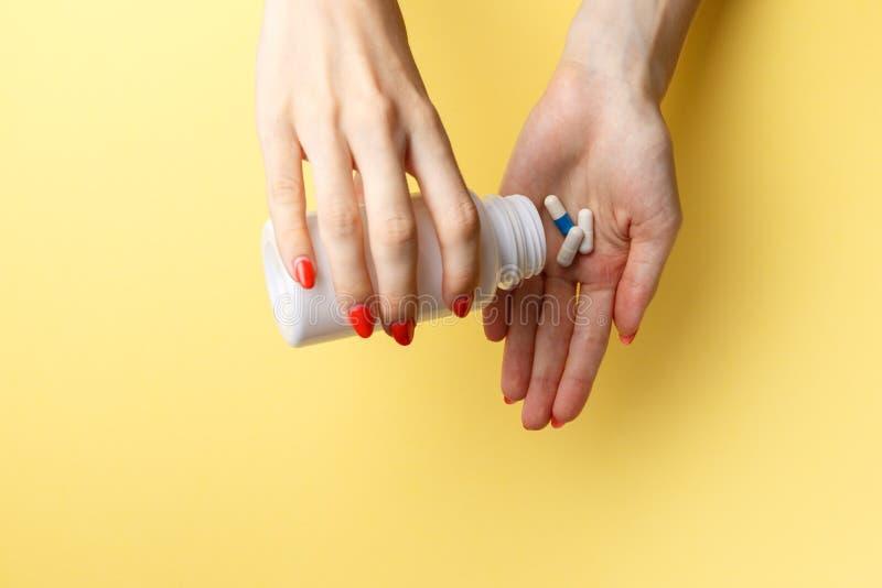 De pillen van de vrouwenholding op hand Geneeskunde en gezondheidszorgconcept Hand die pillen voor de pijn van een fles op gele a stock afbeeldingen