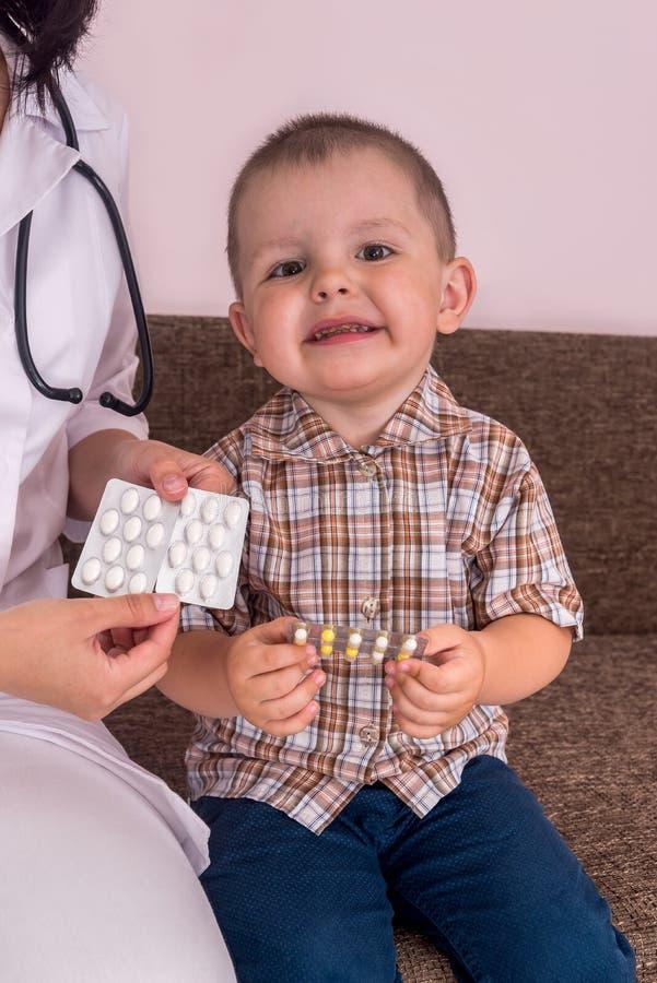 De pillen van weinig jongensholding in blaar in handen royalty-vrije stock foto