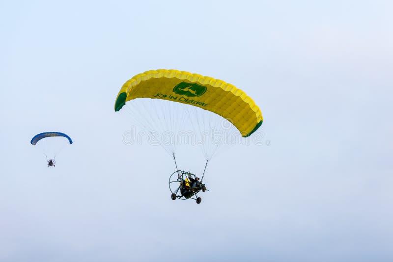 De pilot- flugorna på motoriserad hoppa fallskärm på en pilot för feThe för ballong för varm luft som flugor på motoriserad hoppa royaltyfria foton
