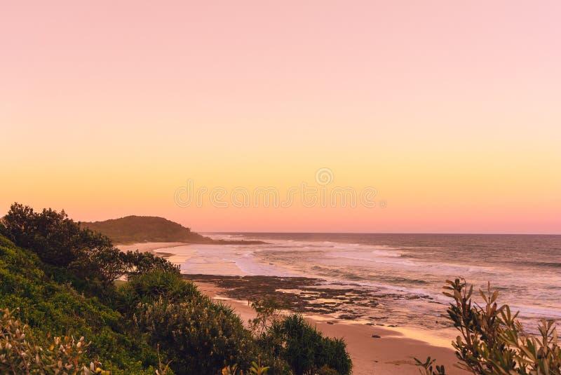 De Pinkzonsondergang in de zomertijd op het strand in Ballina met oceaanmening en het heuvelige landschap, Byron B stock fotografie