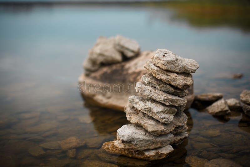 De piramide die van de rotssteen zen in het meer/de rivier blijven royalty-vrije stock foto
