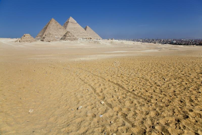 De piramides van Giza met de stad royalty-vrije stock afbeelding