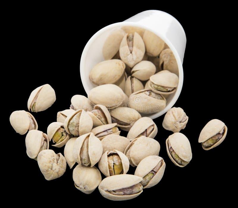 De pistaches vormen zoute noten tot een kom morsten geïsoleerde zwarte royalty-vrije stock foto