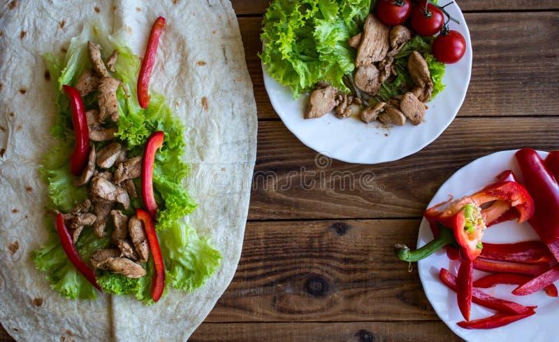 De pitabroodje geroosterde peper van vleestomaten op een plaat en een salade stock foto's