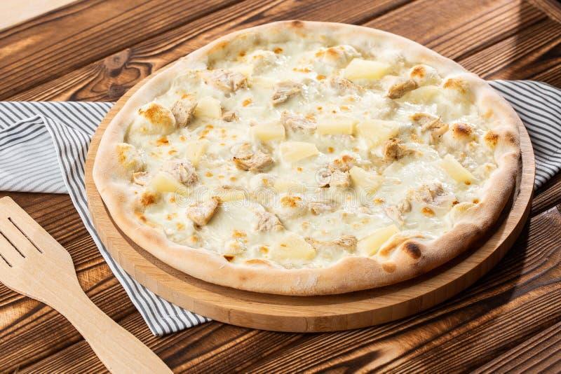 De pizza die met saus wordt bedekt, de kip, de kaas en de ananas dienen op houten plaat op houten lijst Foto van Hawaiiaanse pizz stock afbeeldingen