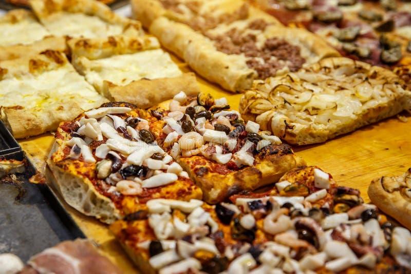 De pizza haalt stukken op een box, Traditionele Italiaanse Focaccia met tomaten, zwarte olijven en kaas weg royalty-vrije stock afbeeldingen