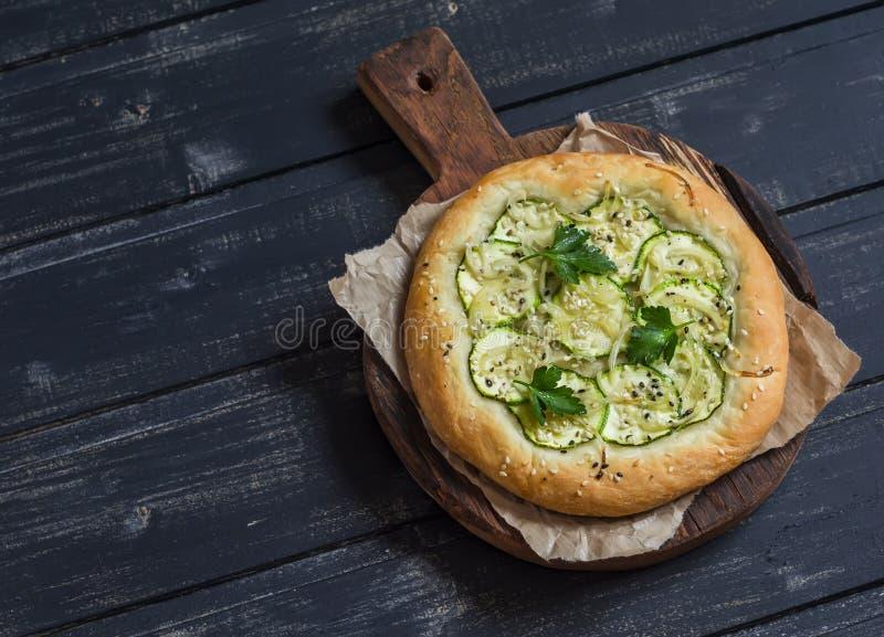 De pizza van de veganistcourgette op een rustieke scherpe raad op donkere houten achtergrond royalty-vrije stock foto's