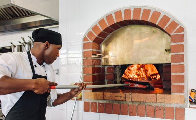 De pizza van het chef-kokbaksel in hout in brand gestoken oven stock foto