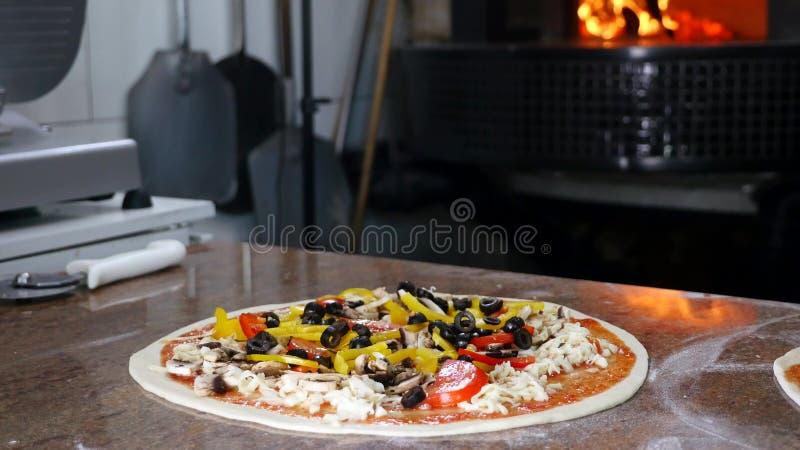 De pizza van het chef-kokkruiden met verse bovenste laagjes, sluit omhoog, langzame motie stock foto