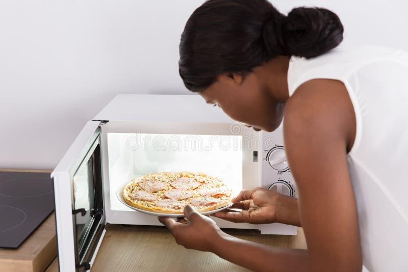De Pizza van het vrouwenbaksel in Magnetron stock afbeeldingen