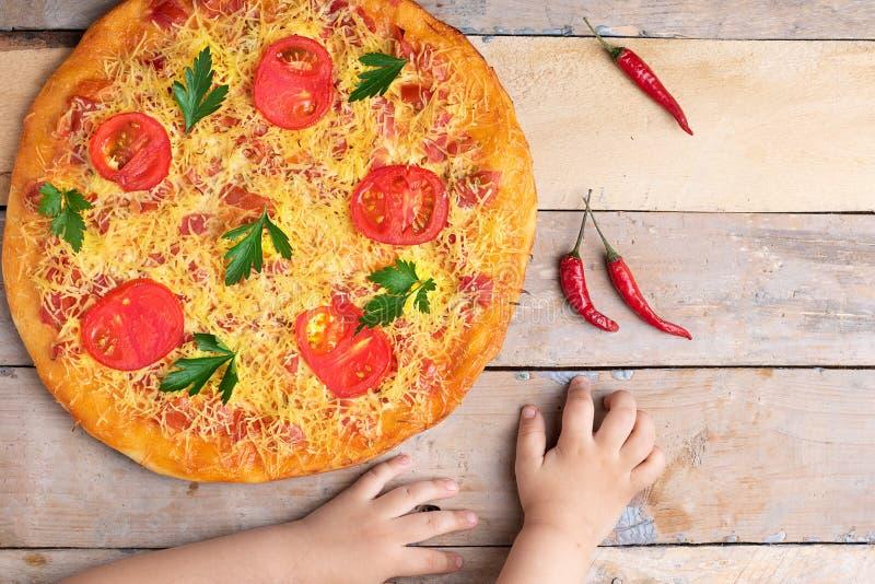 De pizza van veganistmargarita met kaas en tomaten op houten lijst, jonge geitjeshanden, hoogste mening en plaats voor tekst stock foto