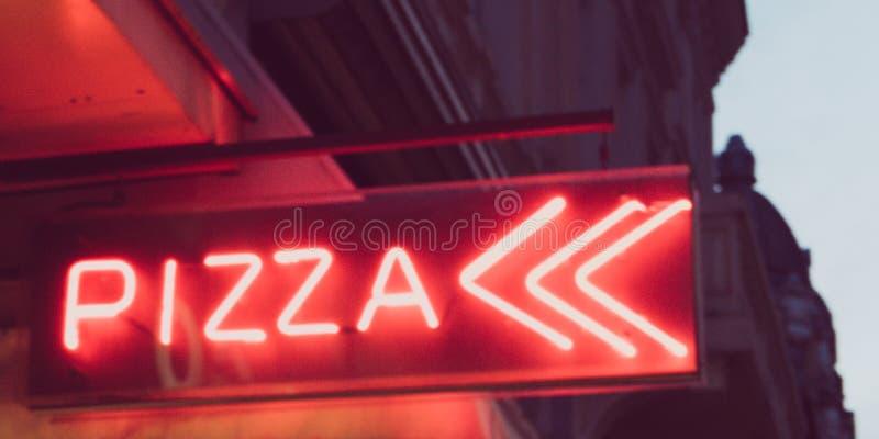 De pizzateken van het nacht lichtrood neon in de straat stock fotografie