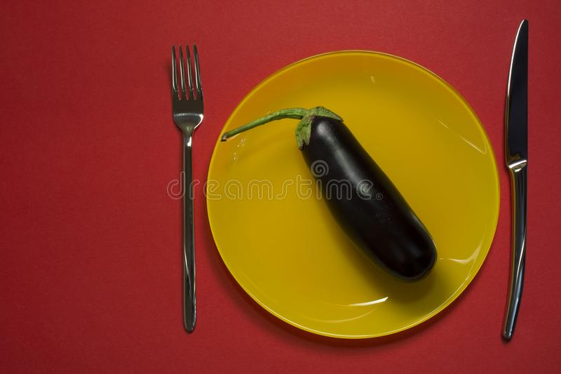 De plaat hoogste mening van het dieetconcept Aubergine op gele lege plaat met vork en mes op rode achtergrond royalty-vrije stock fotografie