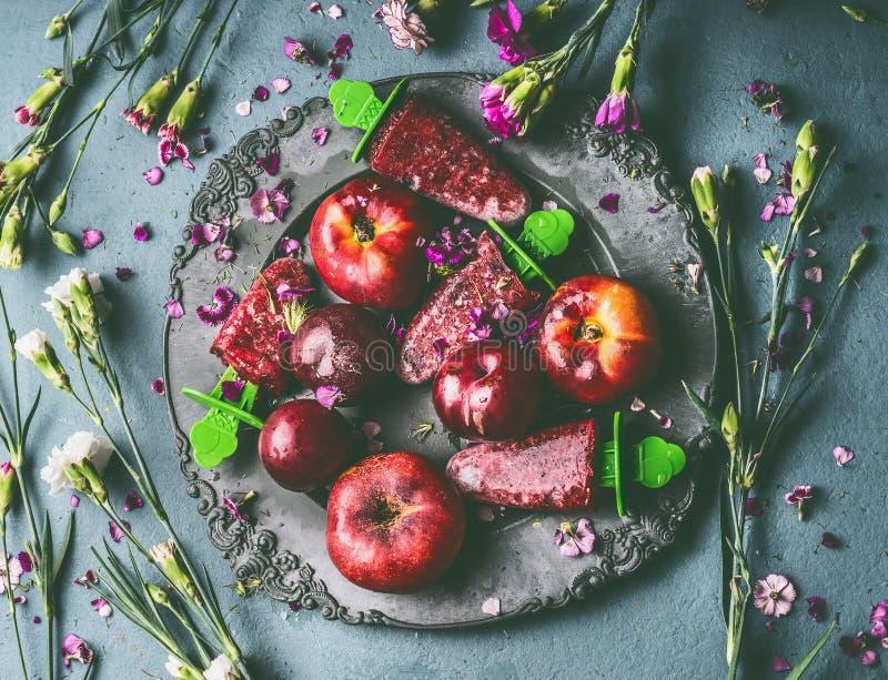 De plaat met eigengemaakte rode vruchten roomijs of Ijslolly op de rustieke achtergrond van de keukenlijst met tuin bloeit royalty-vrije stock foto