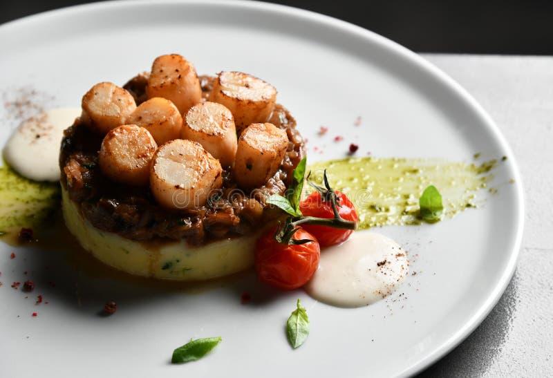 De plaat met geroosterde kammosselen met botercitroen kruidige saus stampte aardappels en tomaten fijn stock afbeeldingen