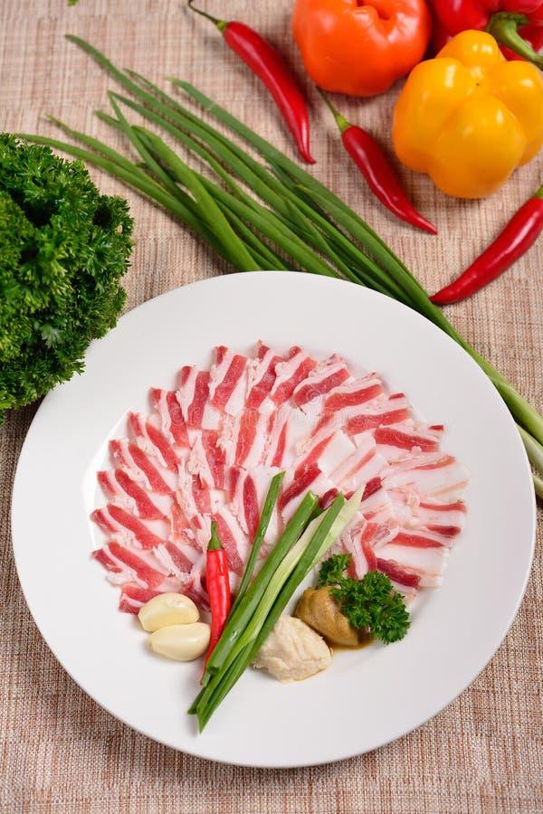 De plaat met vleesknipsel, stroken van bacon en gesneden reuzel, saus, maakt groen Het concept Russisch Oekraïens restaurant Vlak royalty-vrije stock fotografie