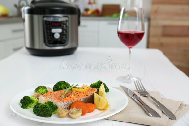 De plaat met zalmlapje vlees en versiert voorbereidingen getroffen in multikooktoestel stock foto's