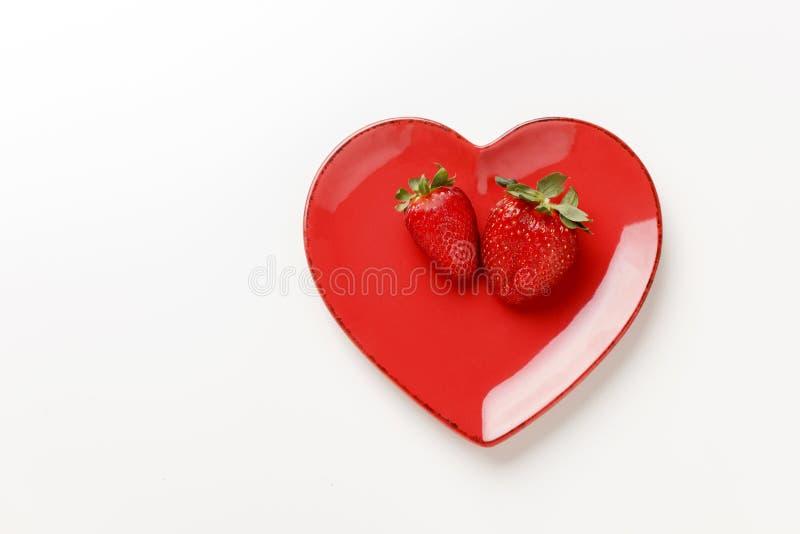 De plaat van de hartvorm met verse aardbeien op wit stock foto's