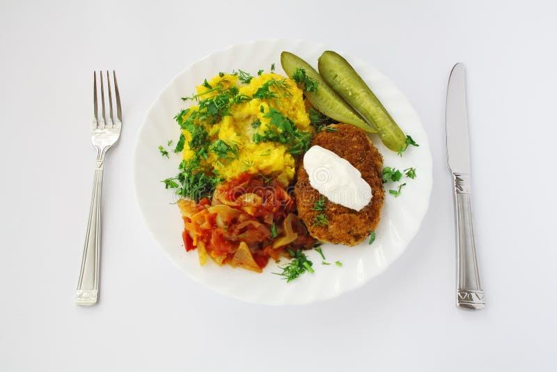 De plaat van het diner met maaltijd die met mes en vork wordt gediend royalty-vrije stock afbeeldingen