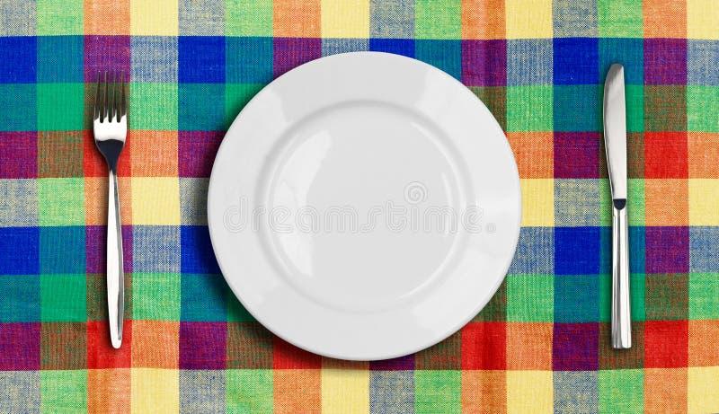 De plaat van het mes en vork veelkleurig tafelkleed stock foto