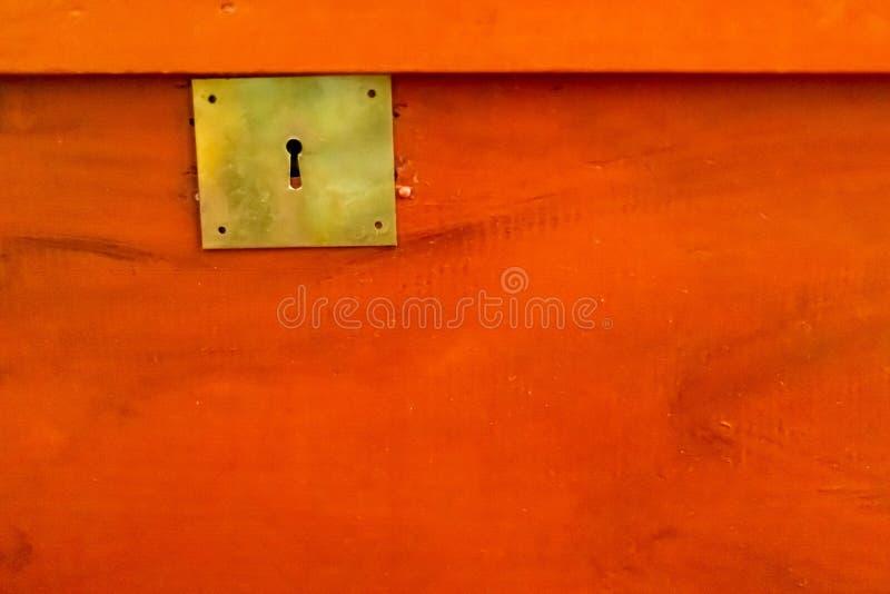 De plaat van het metaalslot op rode houten boomstam stock afbeelding