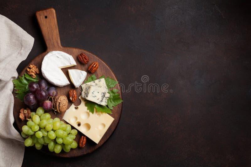 De plaat van de kaas met druiven en noten stock foto's
