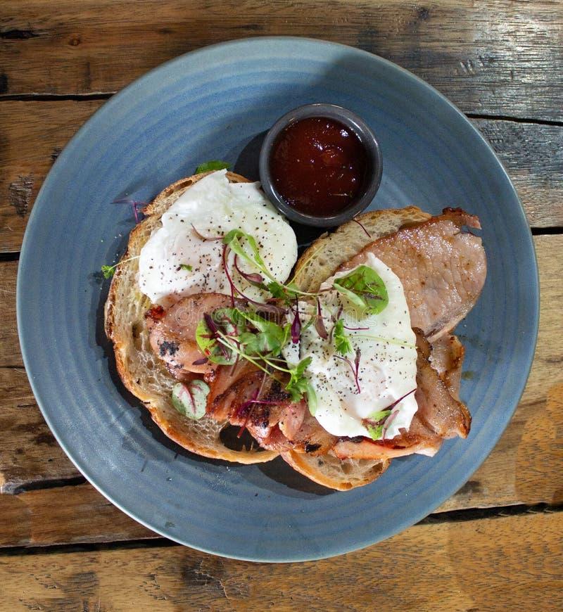 De plaat van de ontbijtmaaltijd van voedsel het bestaan uit stroopte eieren met bacon, toost, saus en versiert reeks boven op hou royalty-vrije stock foto