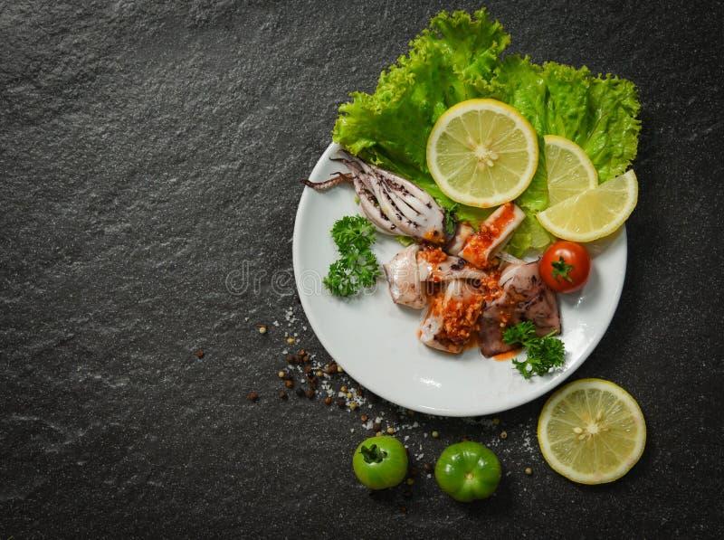 De plaat van de pijlinktvissalade met de de kruidige kruiden en kruiden dat van de Spaanse peperssaus wordt gediend stock afbeelding