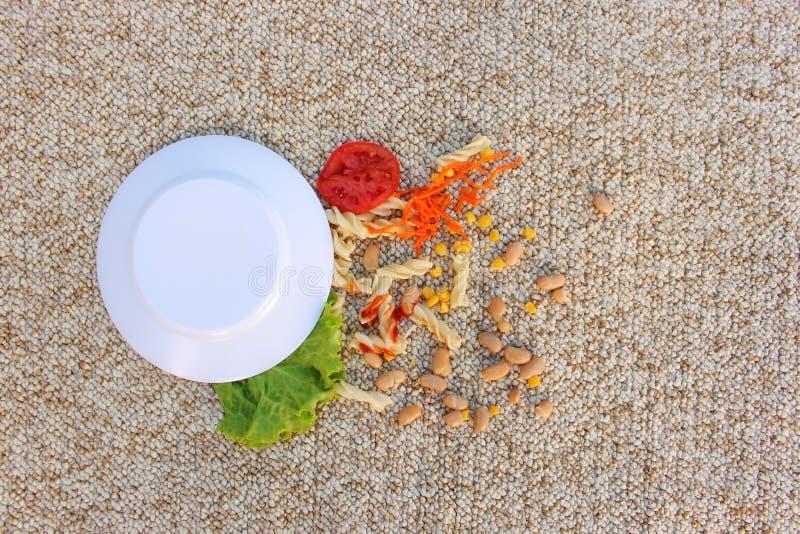 De plaat van voedsel viel op tapijt stock afbeeldingen