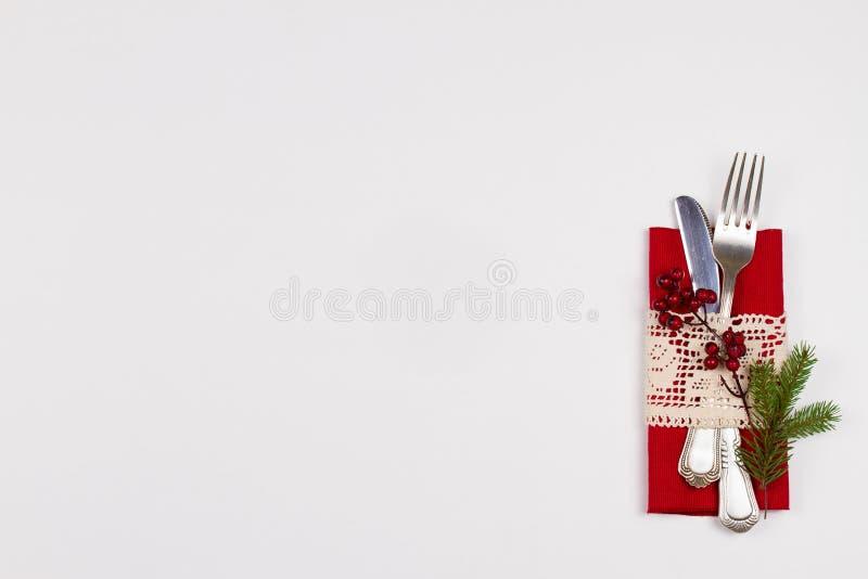 De plaats die van de Kerstmislijst met bestek, pijnboomtak en lint plaatsen De wintervakantie en feestelijke achtergrond stock foto