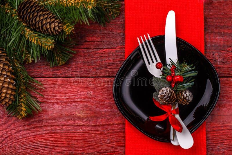 De plaats die van de Kerstmislijst met rood servet, zwarte plaat, wit vork en mes, verfraaide twijg plaatsen van maretak en stock afbeelding