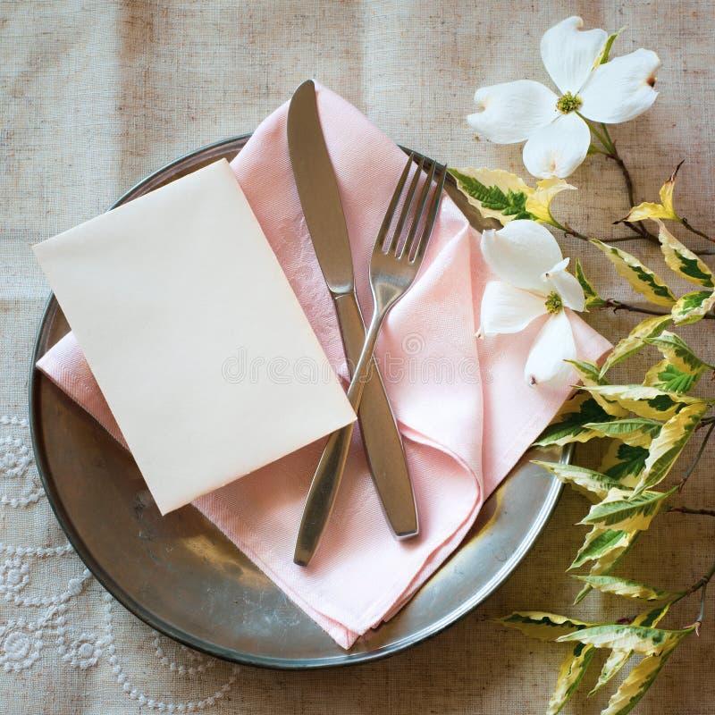 De Plaats die van de de lentelijst met kornoelje plaatsen bloeit, lichtrose servet, tafelzilver en een verticale lege kaart voor  royalty-vrije stock foto