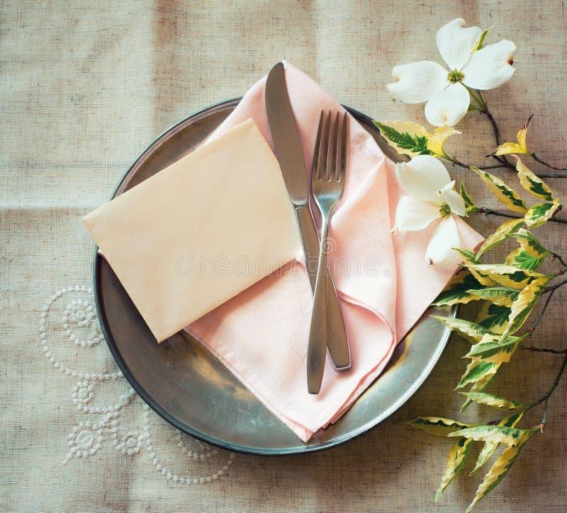 De Plaats die van de de lentelijst met kornoelje plaatsen bloeit, roze servet, tafelzilver en een lege kaart voor menu of uitnodi stock foto