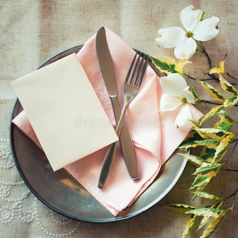 De Plaats die van de de lentelijst met kornoelje plaatsen bloeit, roze servet, tafelzilver en een lege kaart voor menu of uitnodi stock fotografie