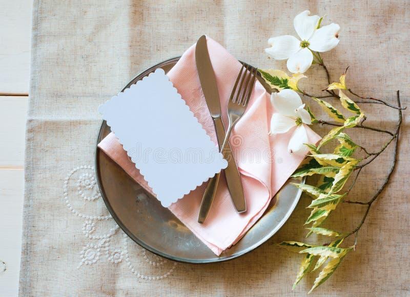 De Plaats die van de de lentelijst met witte bloemen, roze servet, tafelzilver en een lege kaart voor partijmenu of uitnodiging p stock foto