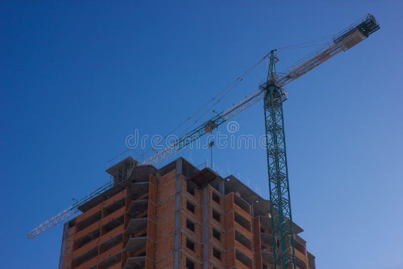 De plaats van de kraan en van de bouwconstructie tegen blauwe hemel royalty-vrije stock afbeeldingen