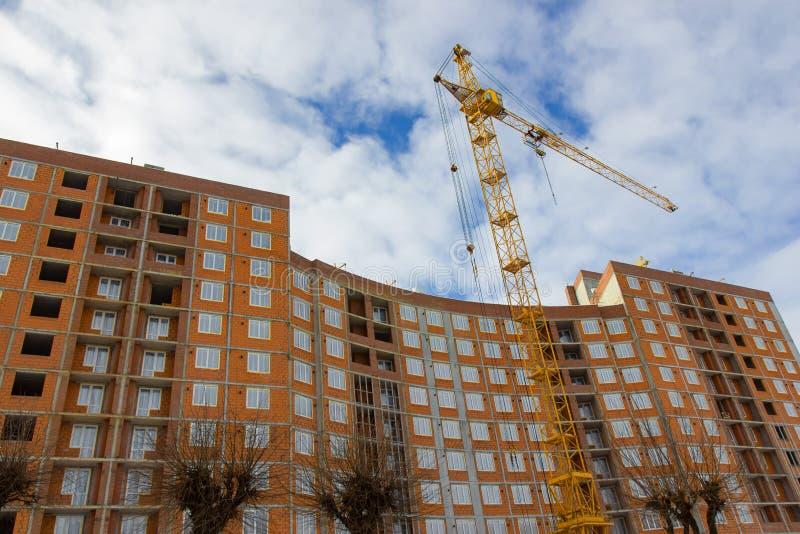 De plaats van de kraan en van de bouwconstructie tegen blauwe hemel stock foto
