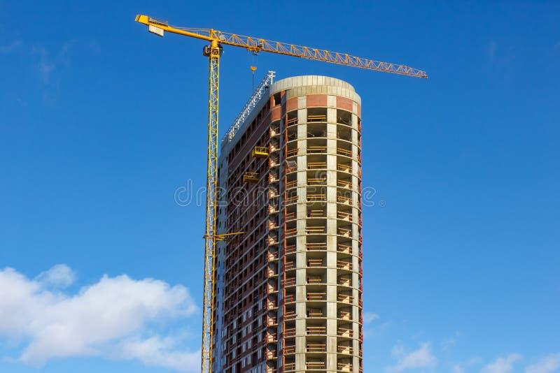 De plaats van de kraan en van de bouwconstructie tegen blauwe hemel stock fotografie